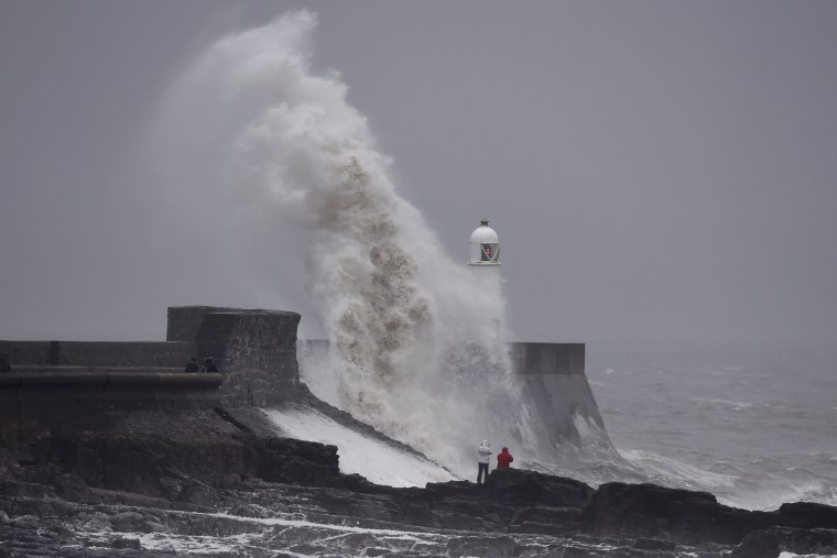 Image: Waves crash over the lighthouse at Porthcawl, Wales