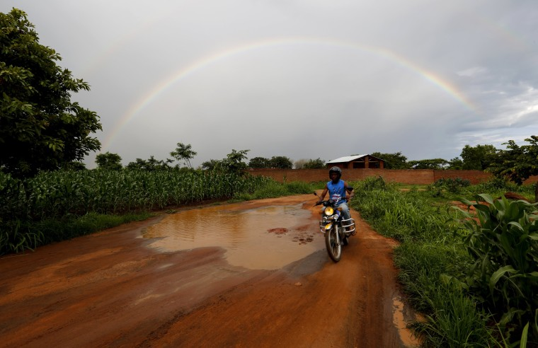 Image: Storm clouds hover as a motorcyclist rides past a field of maize after late rains near Malawi's capital Lilongwe