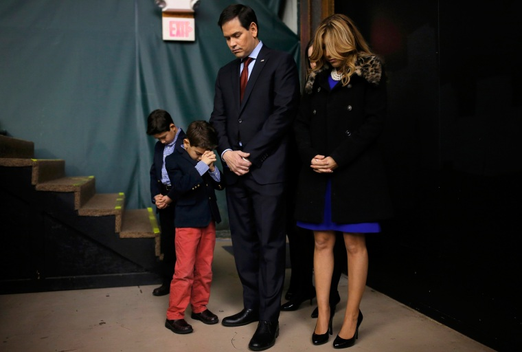 Image: Republican U.S. presidential candidate Marco Rubio prays with his family as they attend the Republican caucus at the 7 Flags Event Center in Clive