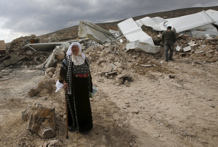Image: A Palestinian woman reacts in front of her house after it was demolished by Israeli bulldozers in the West Bank village of Jimba