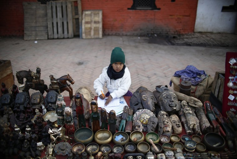 Image: A girl completes her homework sitting at her father's stall on a street of Bashantapur Durbar Square in Kathmandu