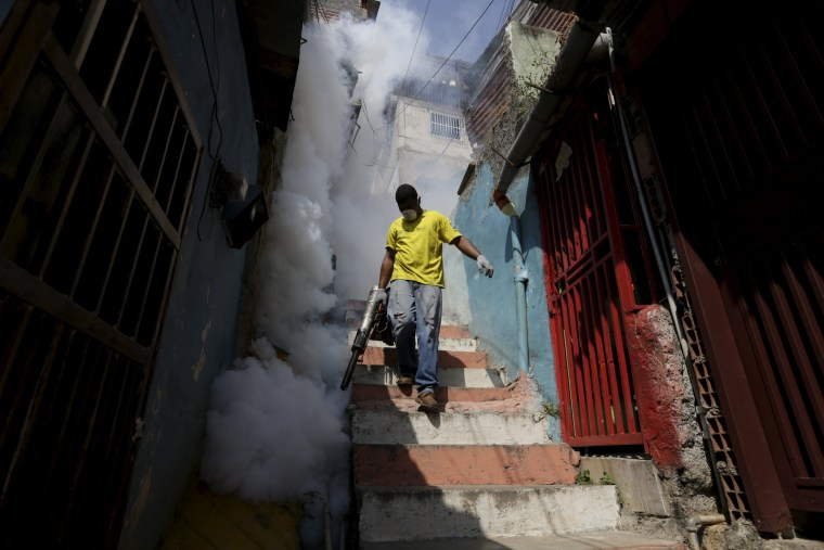 Image: A municipal worker fumigates the Petare slum to help control the spread of the mosquito-borne Zika virus in Caracas