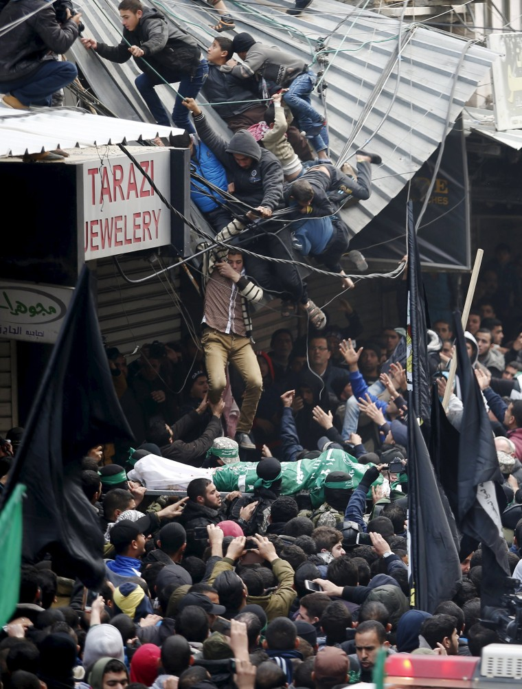 Image: Palestinians fall down from a shop roof during the funeral of seven Hamas gunmen who were killed when a tunnel collapsed close to the Gaza Strip's eastern border with Israel in Gaza City
