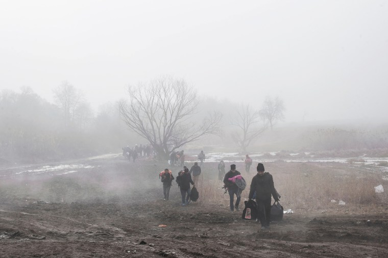 Image: Migrants and refugees walk after crossing the Macedonian border into Serbia