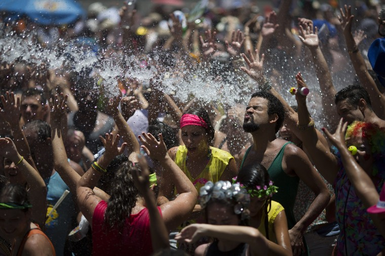 """Image: People cool off in water during the \""""Escravos da Maua\"""" block party"""