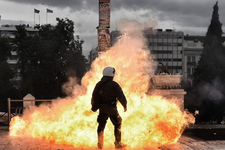 Image: A firebomb explodes beside a riot police member