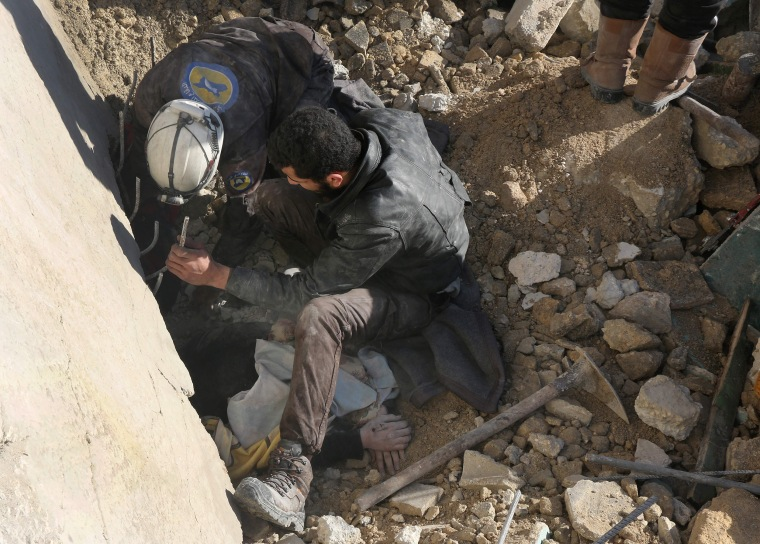 Image: Syrian rescuers remove a victim from under the rubble following a reported air strike on the rebel-held neighborhood of al-Kalasa