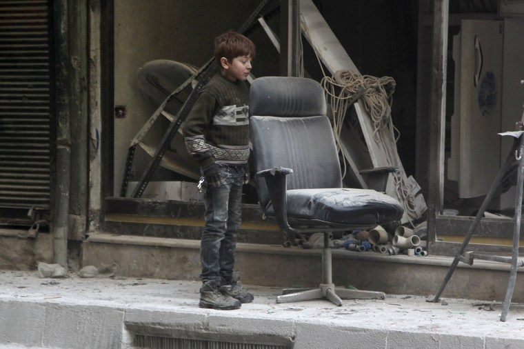 Image: A boy inspects damage after airstrikes by pro-Syrian government forces in the rebel held Al-Shaar neighbourhood of Aleppo, Syria