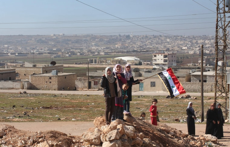 Image: Syrians celebrate as pro-government forces drive through the Shiite town of Zahraa