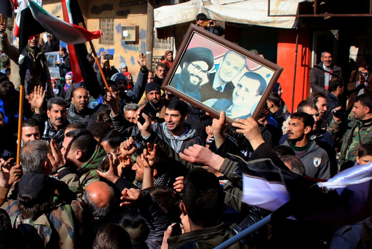 Image: Syrians hold a poster