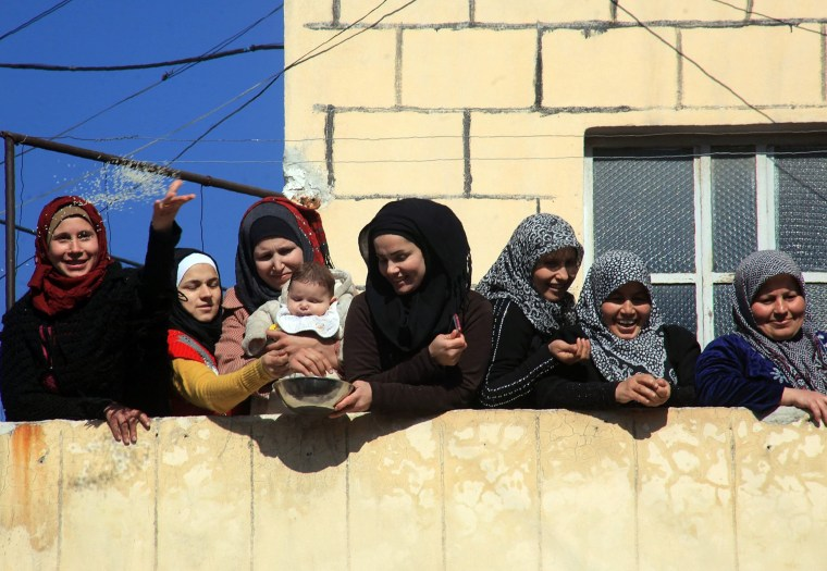 Image: Syrians celebrate after pro-government forces broke an opposition siege in the northern Shiite town of Nubol