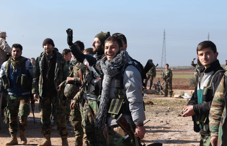 Image: Syrians pro-government forces celebrate after they broke an opposition siege in the northern Shiite town of Zahraa