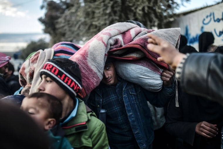 Image: A man carrying belongings on his head looks on as Syrians fleeing the northern embattled city of Aleppo wait
