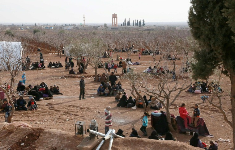 Image: Syrians fleeing the northern embattled city of Aleppo wait in a field