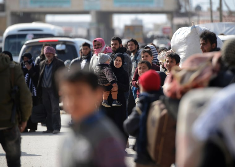 Image: Syrians fleeing the northern embattled city of Aleppo wait at the Bab al-Salama crossing