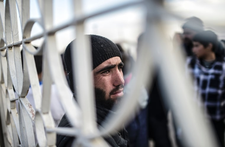 Image: A man stands near a fence as Syrians fleeing the northern embattled city of Aleppo wait