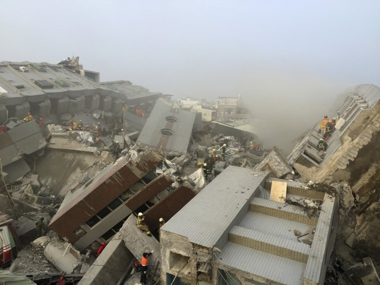 Image: Rescue personnel work at the site where a 17-storey apartment building collapsed, after an earthquake in Tainan