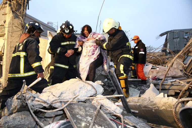 Image: Rescue personnel help a victim at a damaged building after an earthquake in Tainan