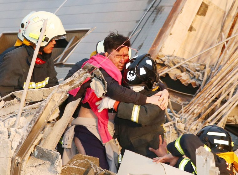 Image: Rescue workers carry out a man from the site where a 17-storey apartment building collapsed after an earthquake hit Tainan
