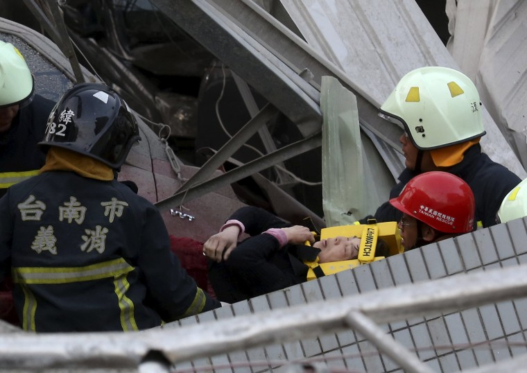 Image: Rescue personnel help a victim at the site where a 17-storey apartment building collapsed, after an earthquake in Tainan