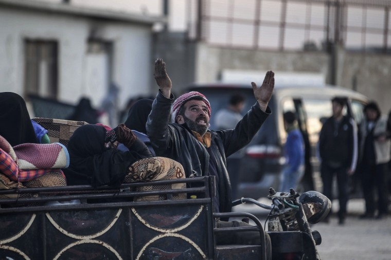Image: A Syrian man gestures as Syrians gather at the border gate with Turkey