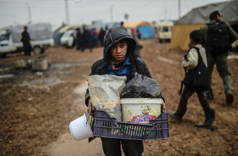 Image: A child carries belongings as refugees arrive at the Turkish border crossing gate