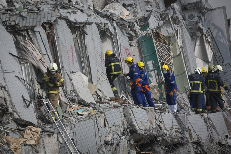 Image: Rescue personnel search for survivors at the site of a collapsed building