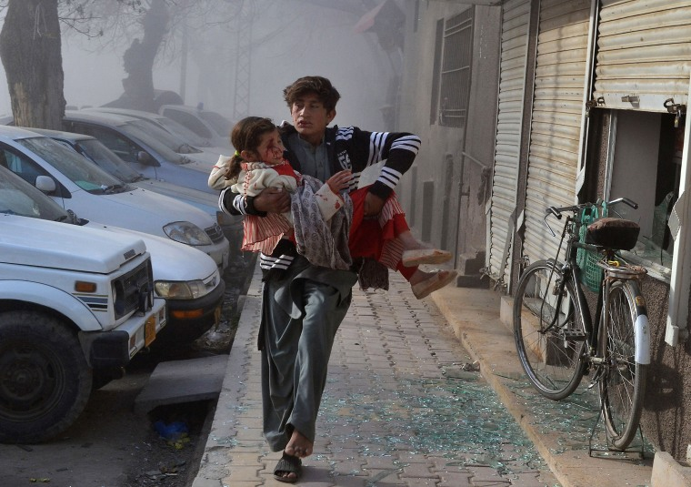 Image: An injured boy carries a girl as he runs towards a safe area a few minutes after a suicide bombing in Quetta