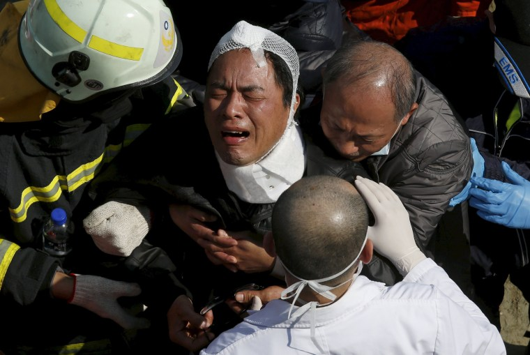Image: A relative cries after his family member was confirmed dead at a 17-storey apartment building that collapsed after an earthquake hit Tainan, southern Taiwan