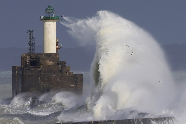 Image: Waves crash against a lighthouse as the wind blows at around 100 kph (62 mph), in Boulogne-sur-Mer