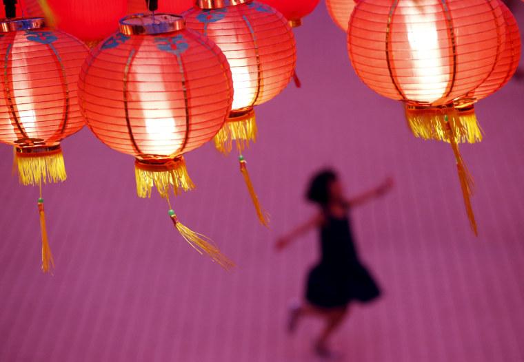 Image: A child plays beneath lanterns