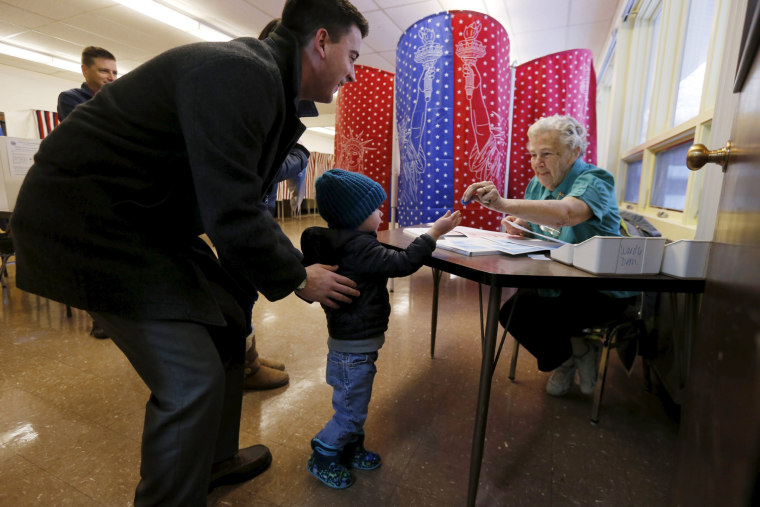 Image: An election official takes a voting token from young Bryan Townsend before handing his father a blank ballot to mark his vote in New Hampshire's presidential primary election at a polling place in Manchester, New Hampshire