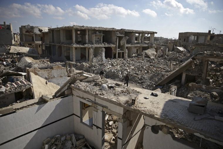 Image: People walk past damaged buildings in the Douma neighbourhood of Damascus