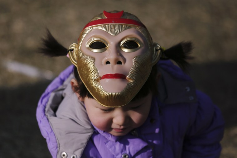 Image: A girl wearing a monkey mask atop her head is seen at the Longtan park as the Chinese Lunar New Year is celebrated in Beijing