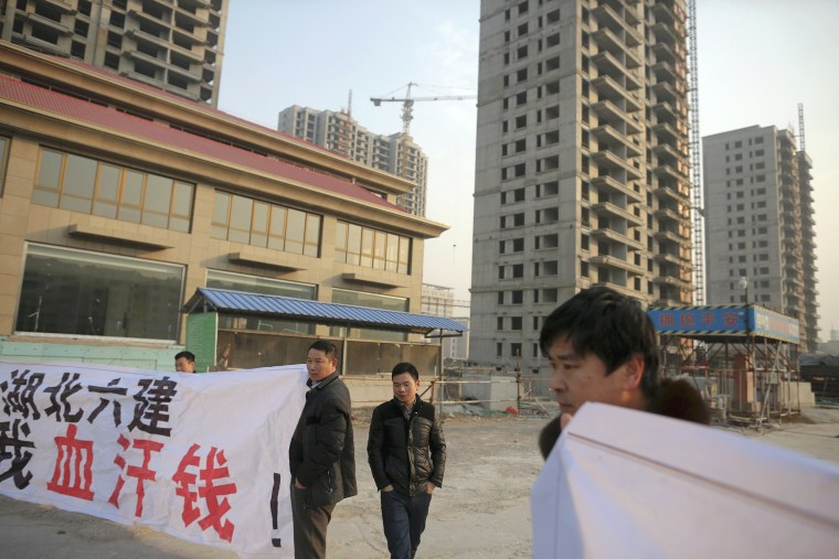 Image: Migrant workers display banners at the construction site of Zixia Garden development complex in Qianan, Tangshan City