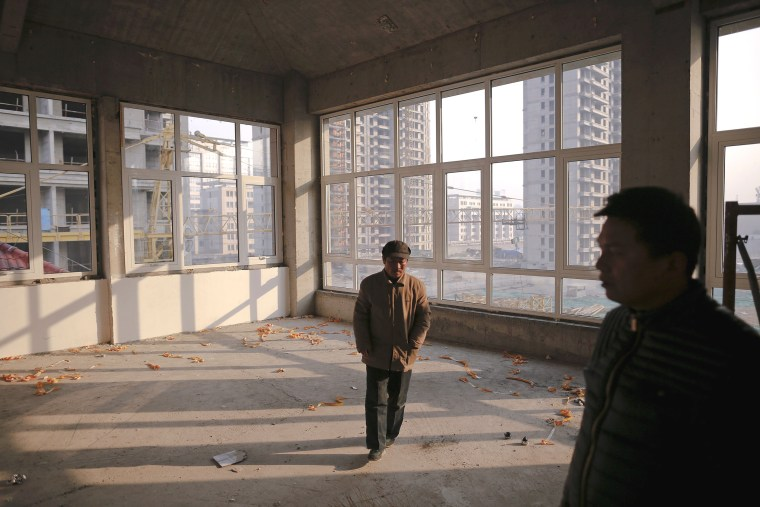 Image: Migrant workers walk inside an unfinished building at the construction site of Zixia Garden development complex in Qianan, Tangshan City