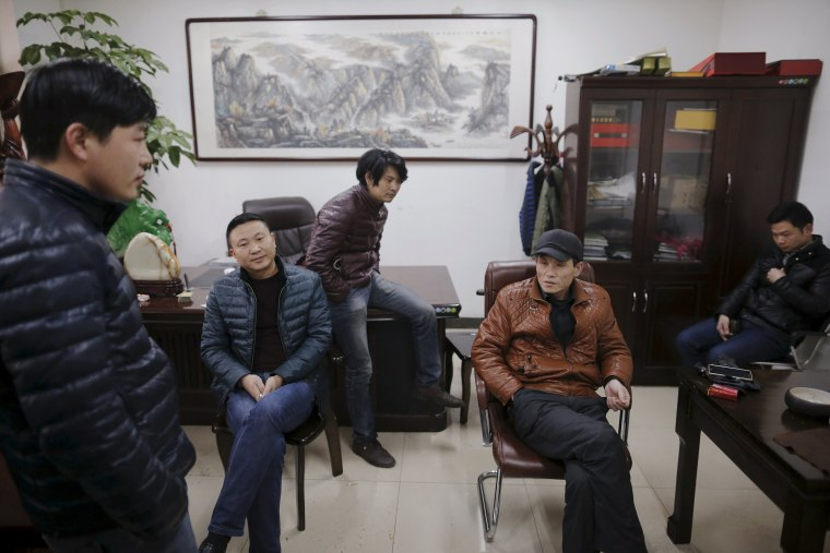 Image: Migrant workers pass time at the offices of a subcontractor company at the construction site of Zixia Garden development complex in Qianan, Tangshan City