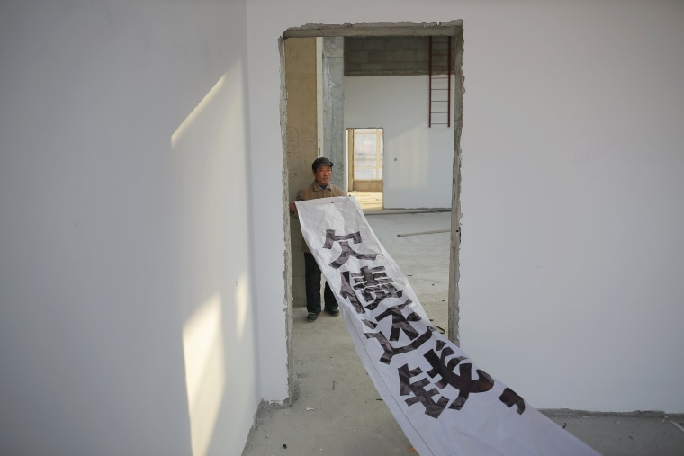 Image: A migrant worker shows a banner inside a building that is under construction as a part of Zixia Garden development complex in Qianan, Tangshan City