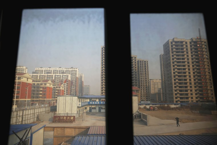 Image: A man is seen from inside the offices of a subcontractor company as he walks through the construction site of Zixia Garden development complex in Qianan, Tangshan City