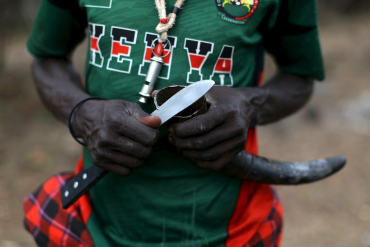 Image: A man cuts a cow horn that will be used to store an anointment for ceremonies