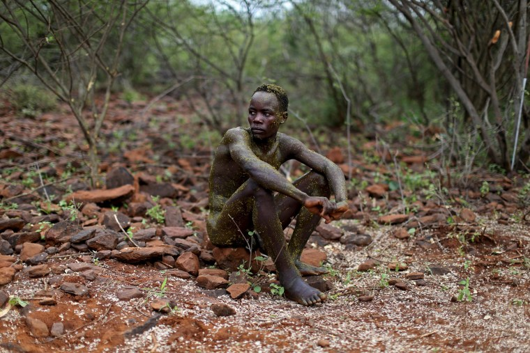 Image: A young Pokot man sits on the ground after having been smeared with the contents of a bull's stomach by elder