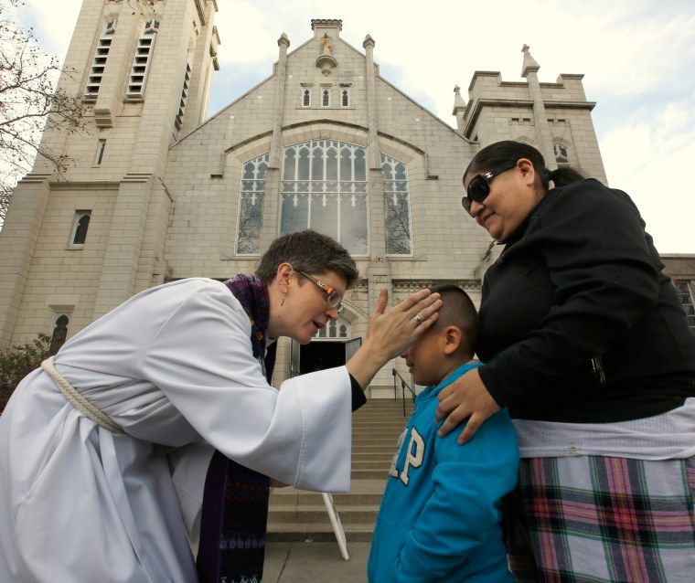 Image: A Pastor places ashes on the forehead of a child accompanied by his mother