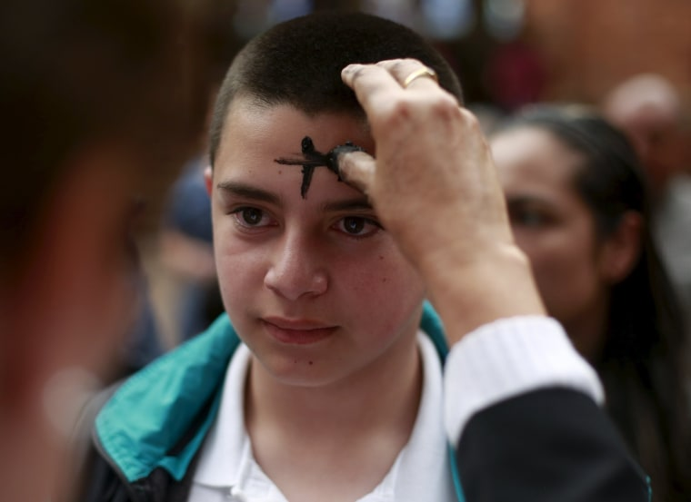 Image: A boys receives a cross of ashes during service