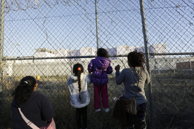 Image: Inmates' relatives hang on to the fence surrounding the Topo Chico prison in Monterrey