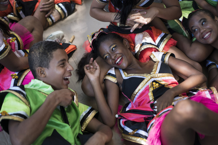 """Image: Young revelers joke with each other as they lay on the shade during the \""""Burial of the Mosquito\"""" carnival"""