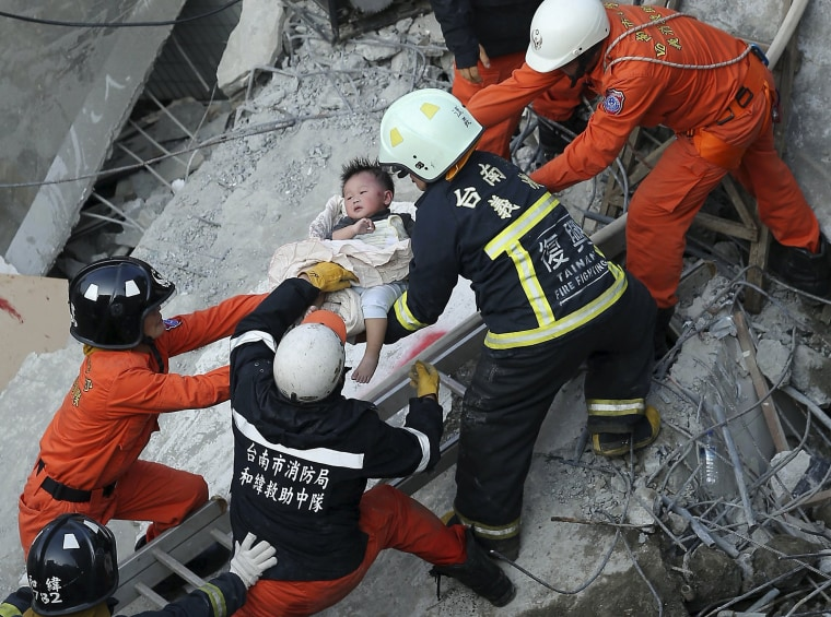 Image: Rescue personnel help a child rescued at the site where a 17-storey apartment building collapsed during an earthquake in Tainan