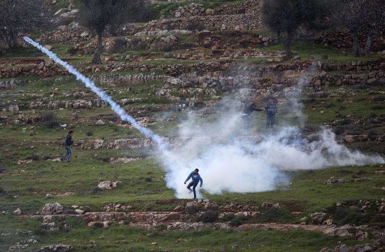 Image: A Palestinian demonstrator throws back a tear gas canister that was fired by Israeli troops during demonstration