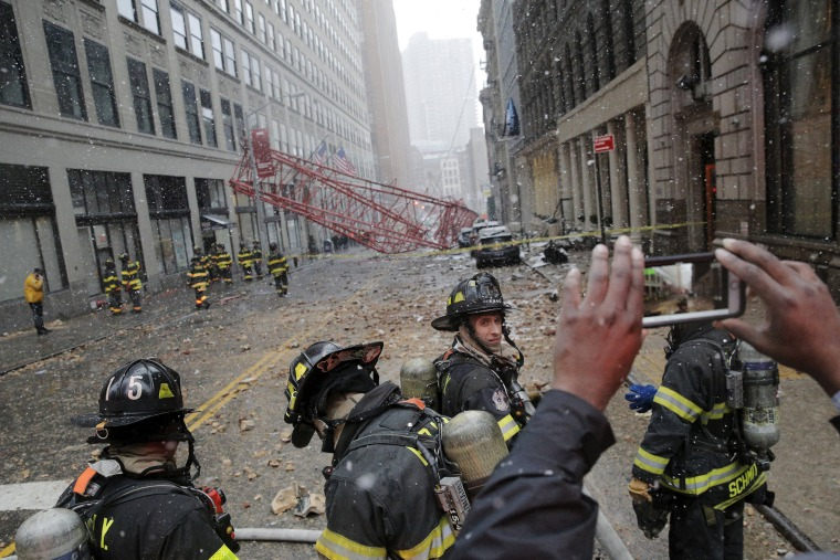 Image: Emergency responders respond to the scene of a 565-foot-tall crane that toppled and flipped upside down, stretching along nearly two city blocks in downtown Manhattan in New York