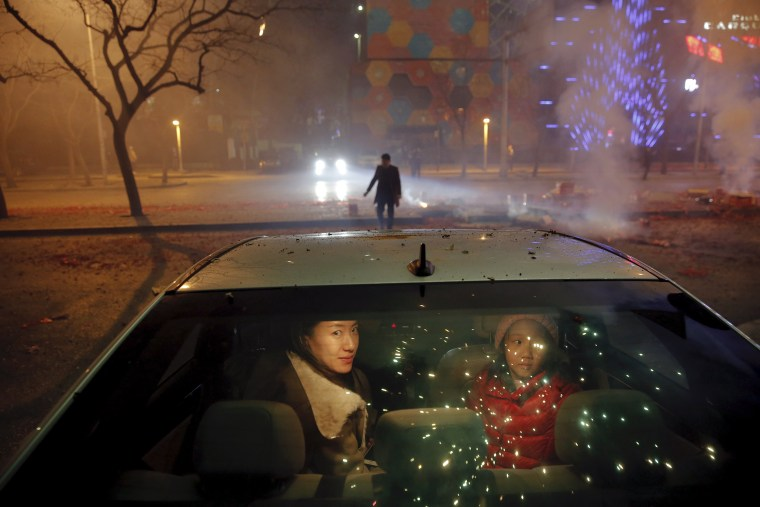 Image: A woman and young girl sit inside a car as firecrackers and fireworks explode celebrating the start of the Lunar New Year