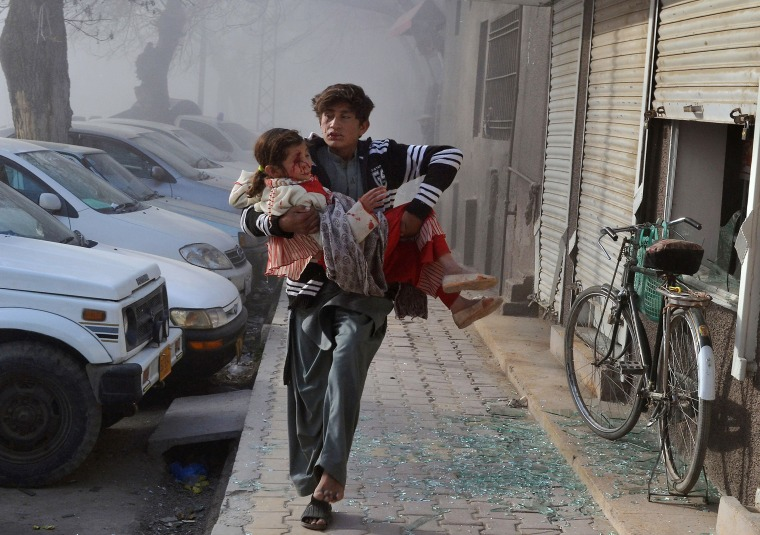 Image: A boy carries an injured girl as he runs towards a safe area a few minutes after the suicide bombing in Quetta